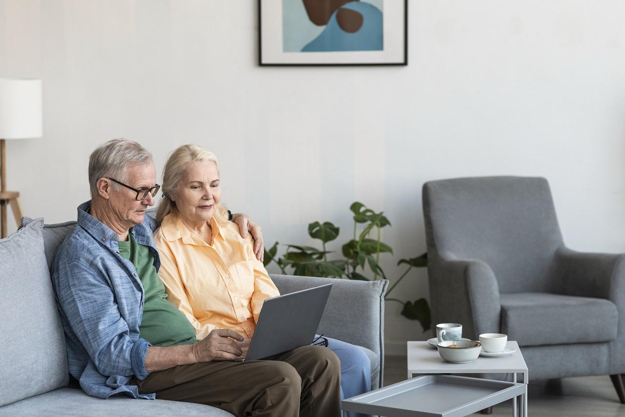 Coppia di pensionati con il computer portatile
