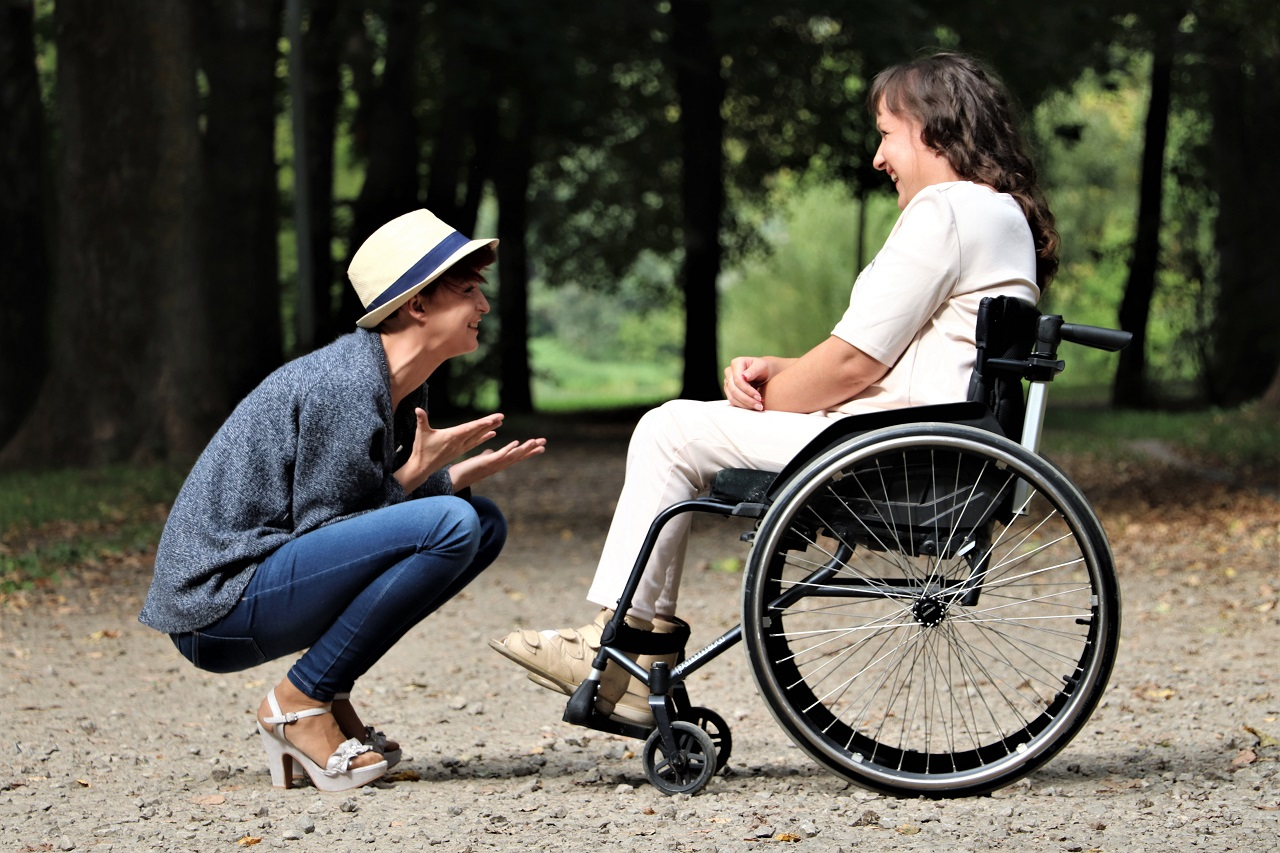 Donna su sedia a rotelle con amica