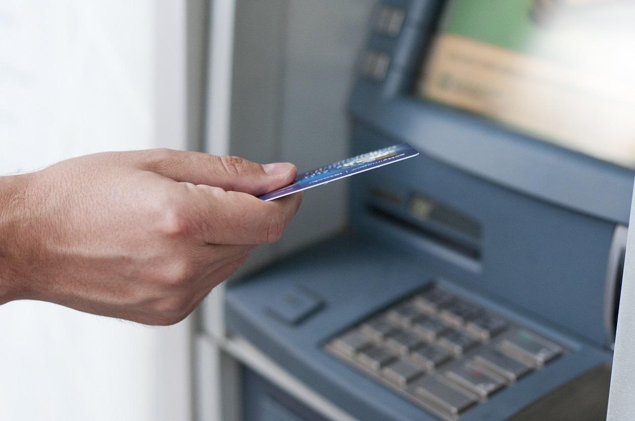 Mano che inserisce la carta di credito nel bancomat per prelevare denaro