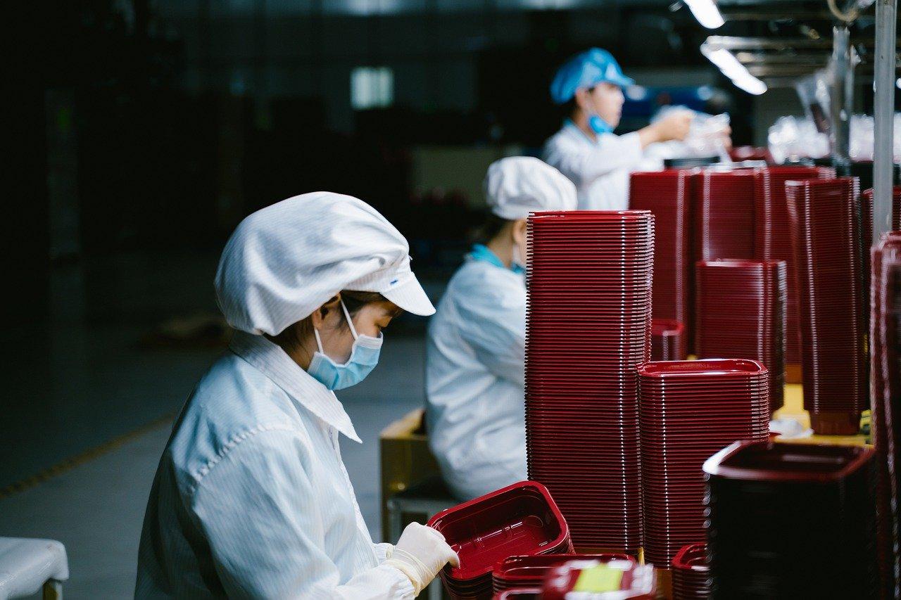 Donna al lavoro in fabbrica con la mascherina