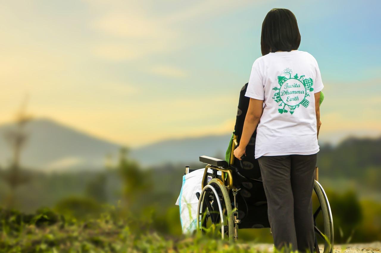 Donna che accompagna invalido su sedia a rotelle